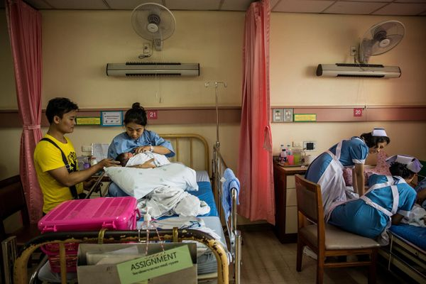 Amugpote, 23, watches his wife Kiengmachu breastfeed their 2-day-passe little one lady, Nam, at Lerdsin Scientific institution in Bangkok on M