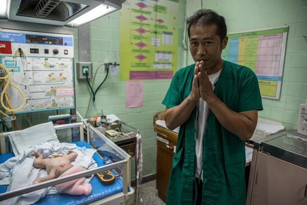 Sai Tlen, 38, meets his recent child daughter after his wife underwent a C-allotment at the Regional Health Promotion Cent