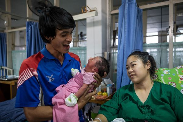 Arif Somsingjai, 30, a development employee, holds his 2-day-passe little one boy Karis, his 2d child, as his wife Chayanid T