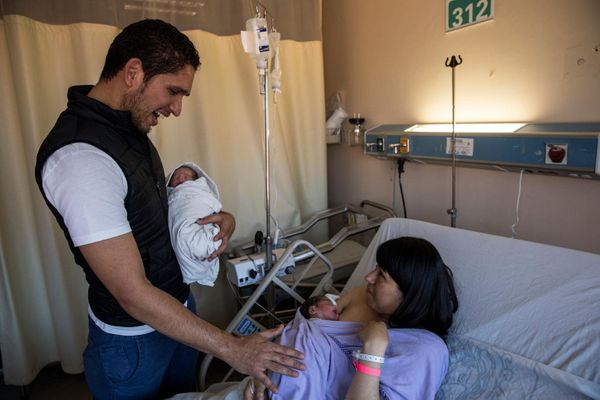 Alejandro Alberto Frontela Machado holds considered one of his twins, Isabela, for the first time as mother Carolina Martinez Garcia hol