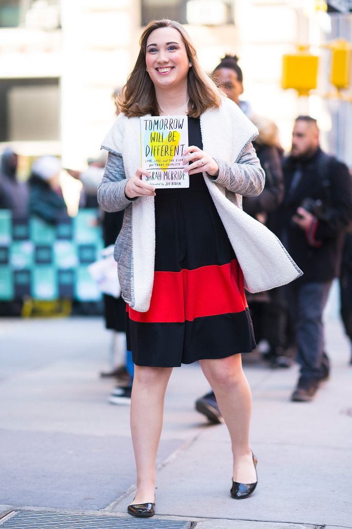 McBride holding her memoir <i>Tomorrow Will Be Different</i>.