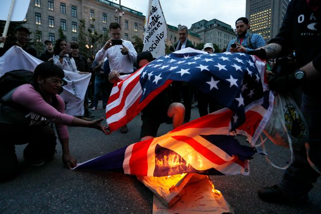 Demonstrators burn US and British flags at a protest march ahead of the G7 summit on June