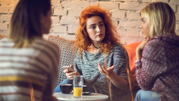 Young serious woman in a cafe communicating with her female friends.