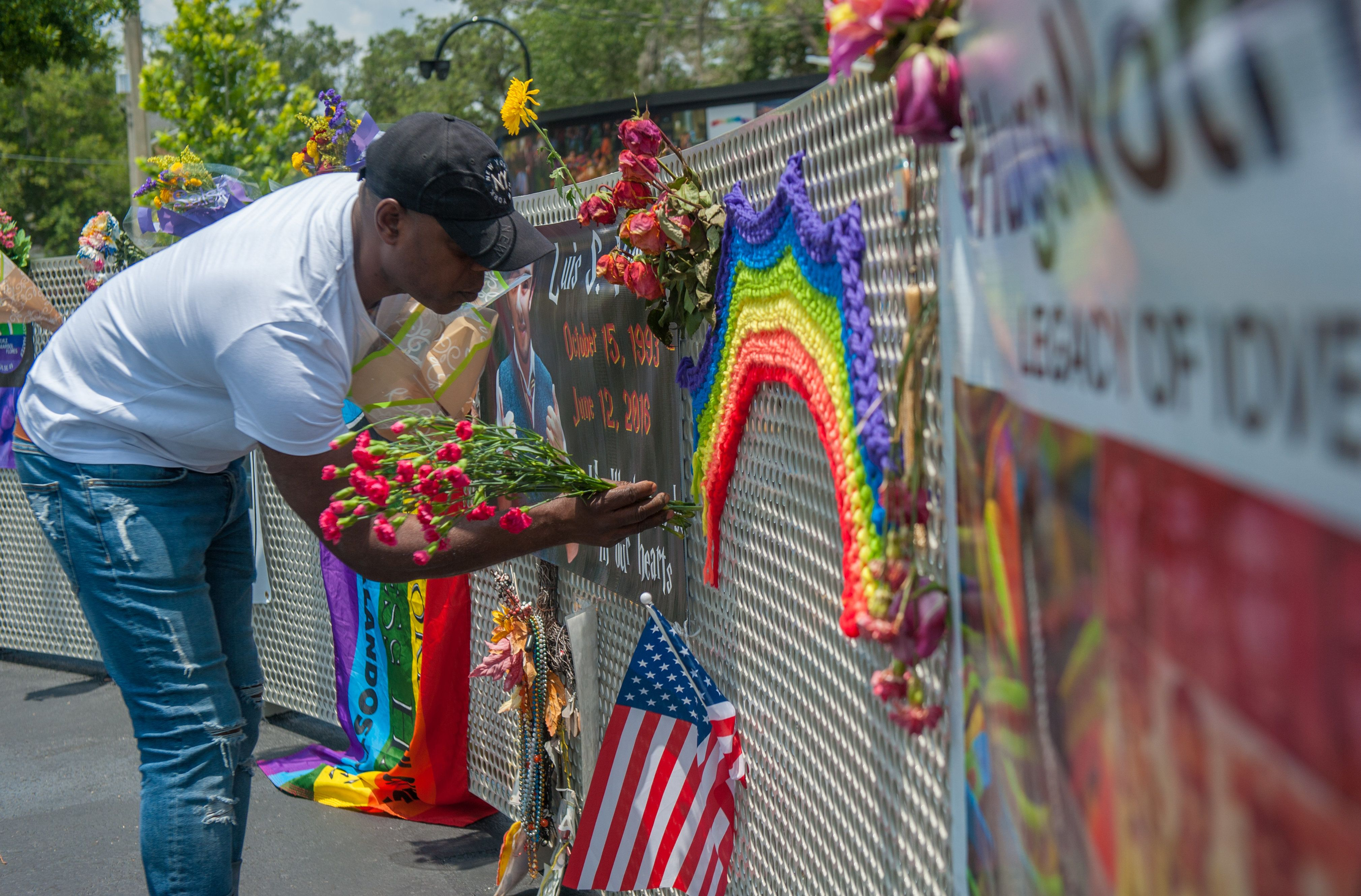 A visitor to the new interim Pulse nightclub memorial leaves flowers in Orlando Florida on June 4, 2018.