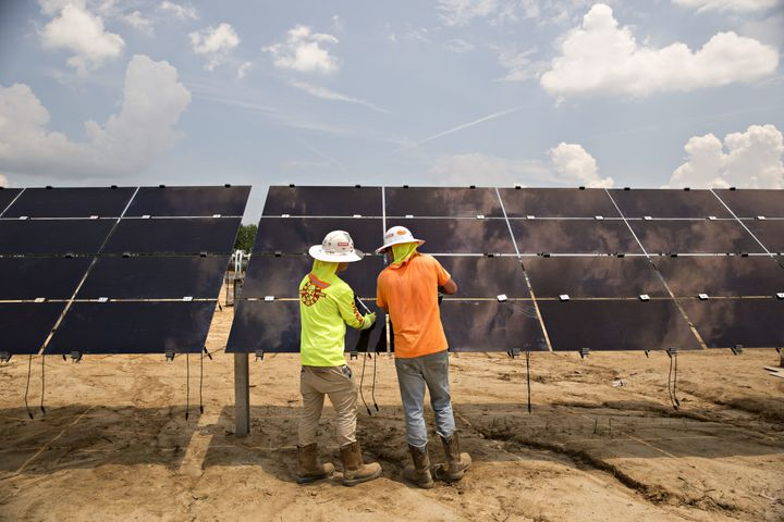 Workers torque mounting brackets on a row of solar panels during construction of a Silicon Ranch Corp. solar generating facility in Milligan, Tennessee, on May 24.