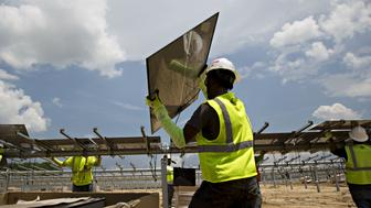 Workers carry solar panel modules during construction of a Silicon Ranch Corp. solar generating facility in Milligan, Tennessee, U.S., on Thursday, May 24, 2018. Large oil companies in Europe are continuing to diversify their holdings and increase clean-energy investments. Royal Dutch Shell Plc agreed in January to buy a 44 percent stake in Silicon Ranch Corp., the Nashville-based owner and operator of U.S. solar plants. Photographer: Daniel Acker/Bloomberg via Getty Images