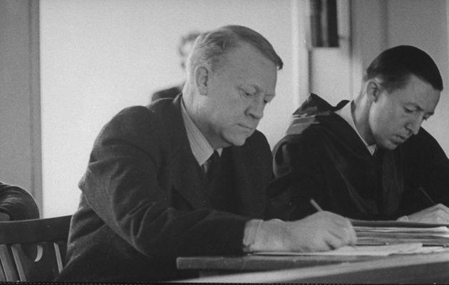 Vidkun Quisling (left) jotting down a note during