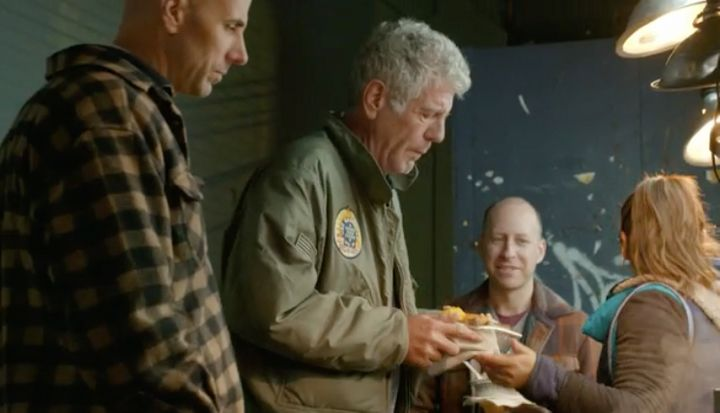 Anthony Bourdain with a plate ofmorcilla and potato cakes in Corona, Queens.