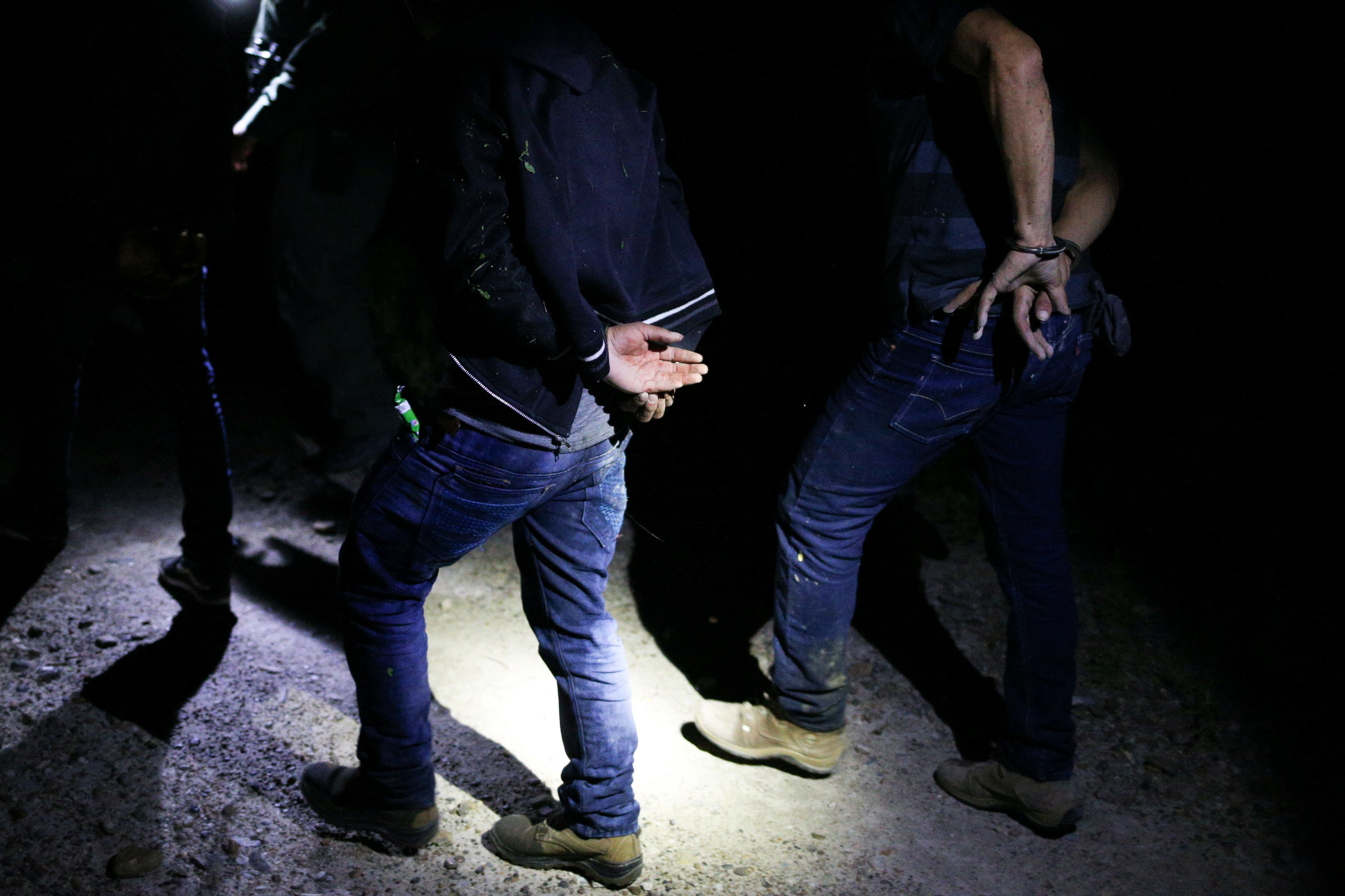 Men who illegally crossed the Mexico-U.S. border are apprehended by U.S. Border Patrol agents near McAllen, Texas, U.S.