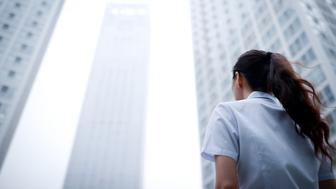 Back View of Business Woman with Skyscraper Office Building Background
