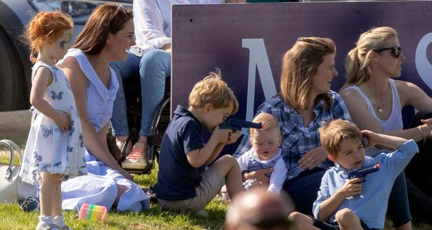 Prince George plays with a toy gun as he sits with his mother, the Duchess of Cambridge.