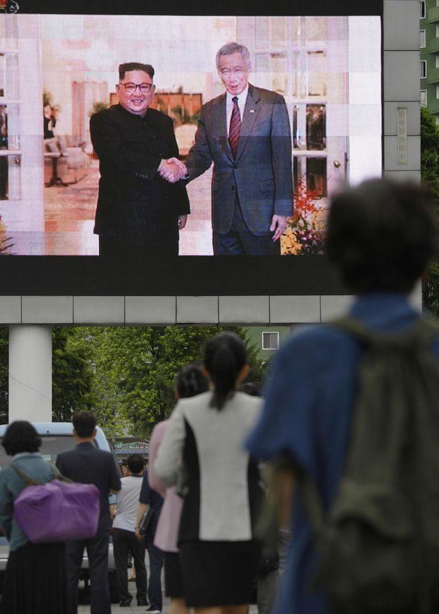 11일 평양 시내 스크린을 통해 방송된 김정은 국무위원장의 싱가포르 방문 관련 뉴스를 지켜보고 있는 주민들의