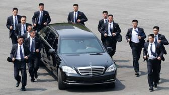 TOPSHOT - North Korean bodyguards jog next to a car carrying North Korea's leader Kim Jong Un returning to the North for a lunch break after a morning session of the inter-Korean summit at the truce village of Panmunjom on April 27, 2018. - North Korean leader Kim Jong Un and the South's President Moon Jae-in sat down to a historic summit on April 27 after shaking hands over the Military Demarcation Line that divides their countries in a gesture laden with symbolism. (Photo by Korea Summit Press Pool / Korea Summit Press Pool / AFP)        (Photo credit should read KOREA SUMMIT PRESS POOL/AFP/Getty Images)