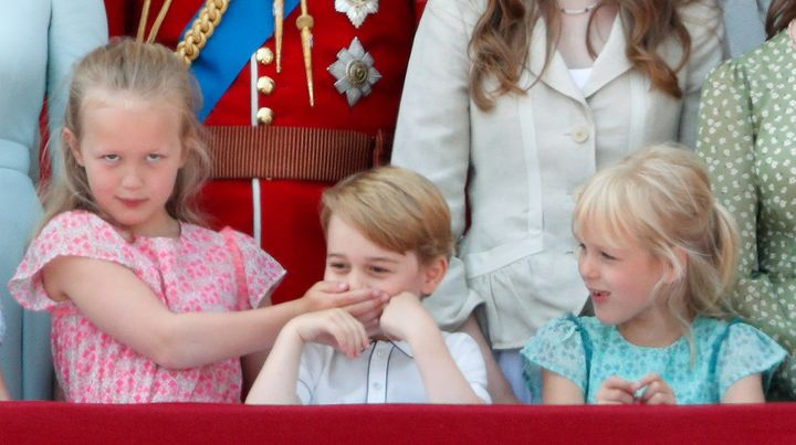 Savannah Phillips puts her hand over Prince George's mouth to keep her younger cousin quiet at Trooping the Color. The parade marks the official birthday of the Sovereign, even though the Queen's actual birthday is on April 21.