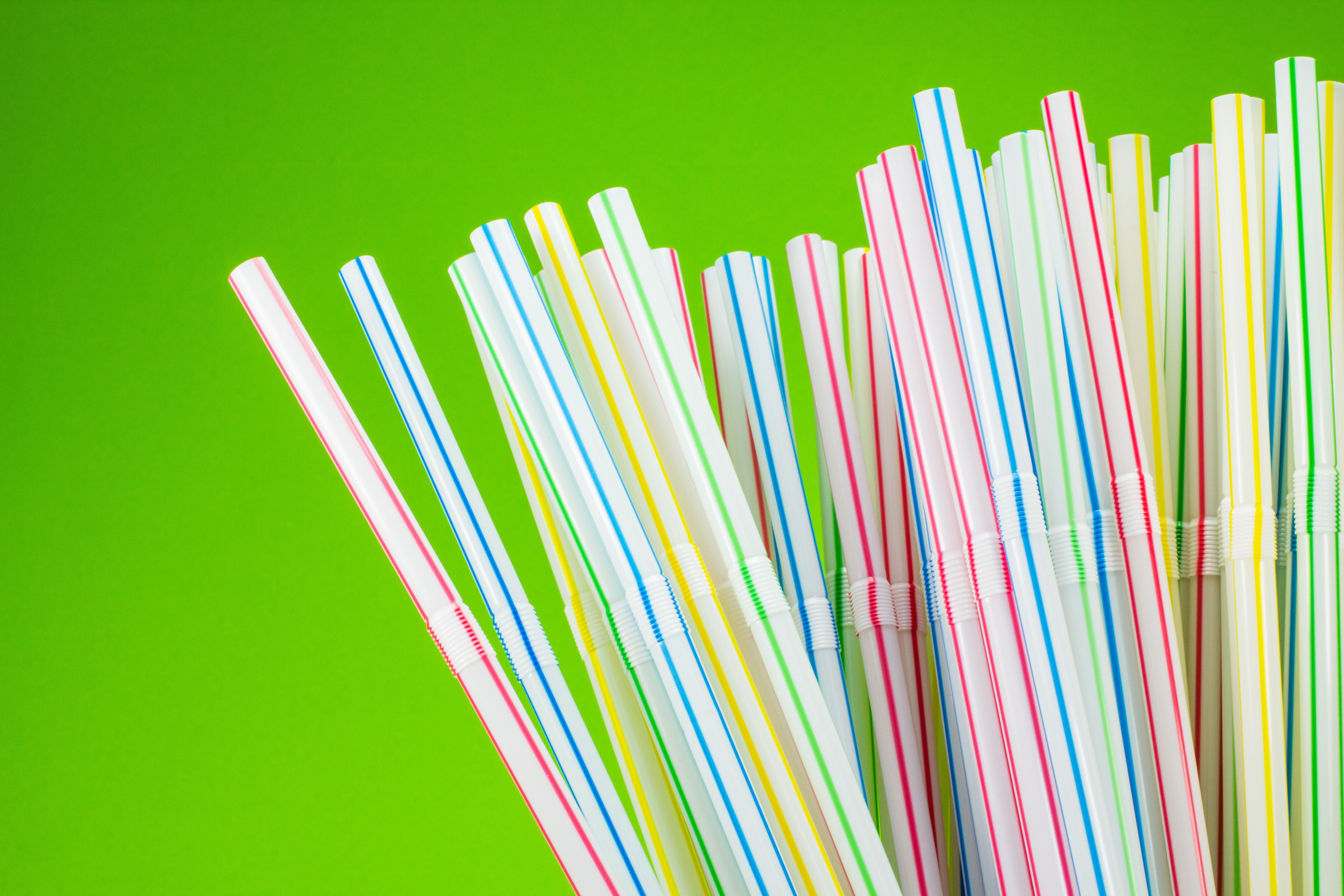 colored drinking straws on green background