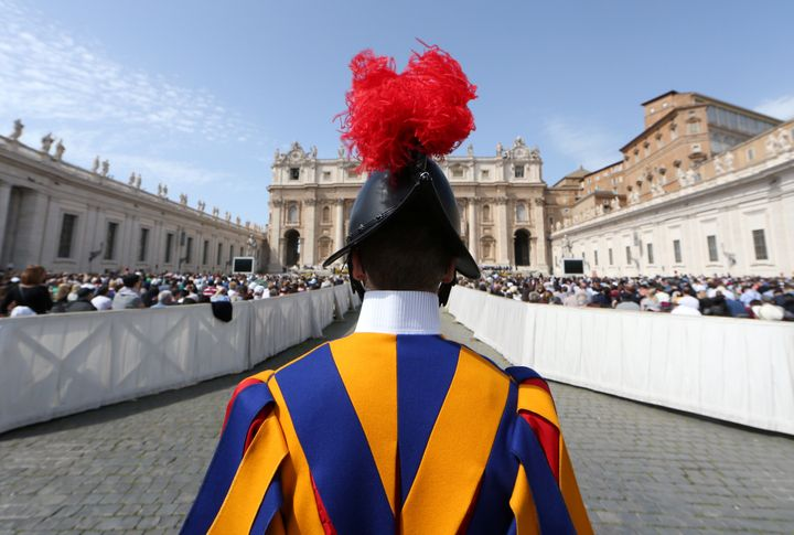 A Swiss guard stands in front of Saint Peter's Basilica during a Holy Mass at the Vatican on April 8, 2018.