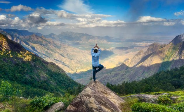 Man doing yoga on the peak of a mountain in Tamilnadu,