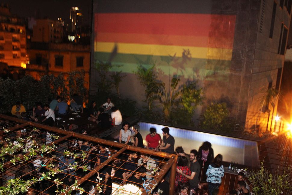 A rooftop party with a rainbow flag projected on the neighboring building during Beirut Pride 2017.
