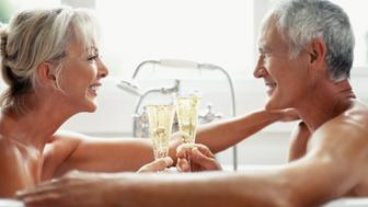 Side view of a romantic mature couple toasting with champagne in a bathtub