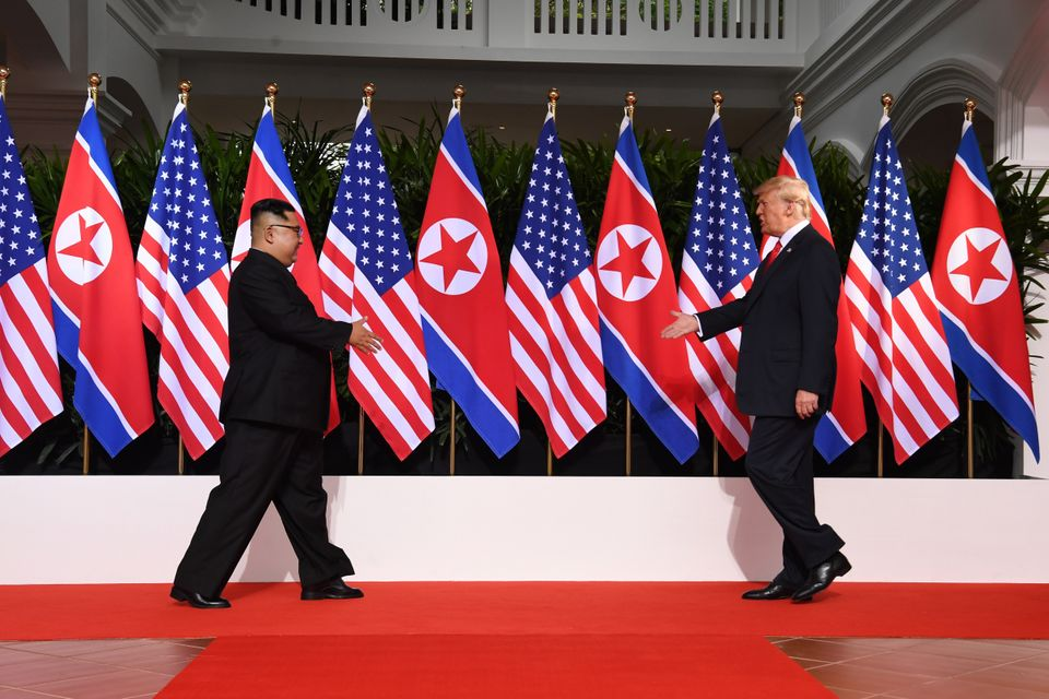 North Korean leader Kim Jong Un and U.S. President Donald Trump extend their hands as they meet in Singapore...