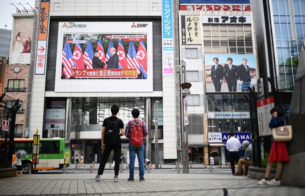 Pedestrians in Tokyo look at a wall-mounted screen displaying live news of the meeting between Trump and Kim on June 12, 2018