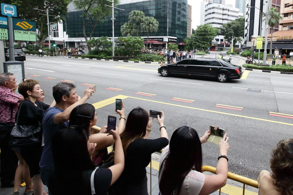 People take photographs as Kim's motorcade leaves the St. Regis hotel.