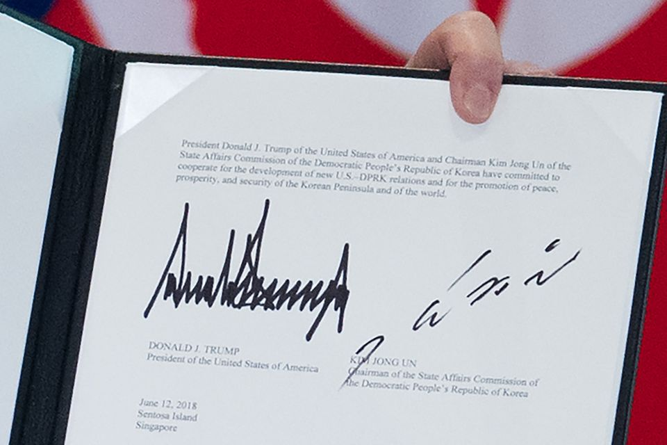 Let's make it official: The signatures of Trump and Kim are displayed following a signing