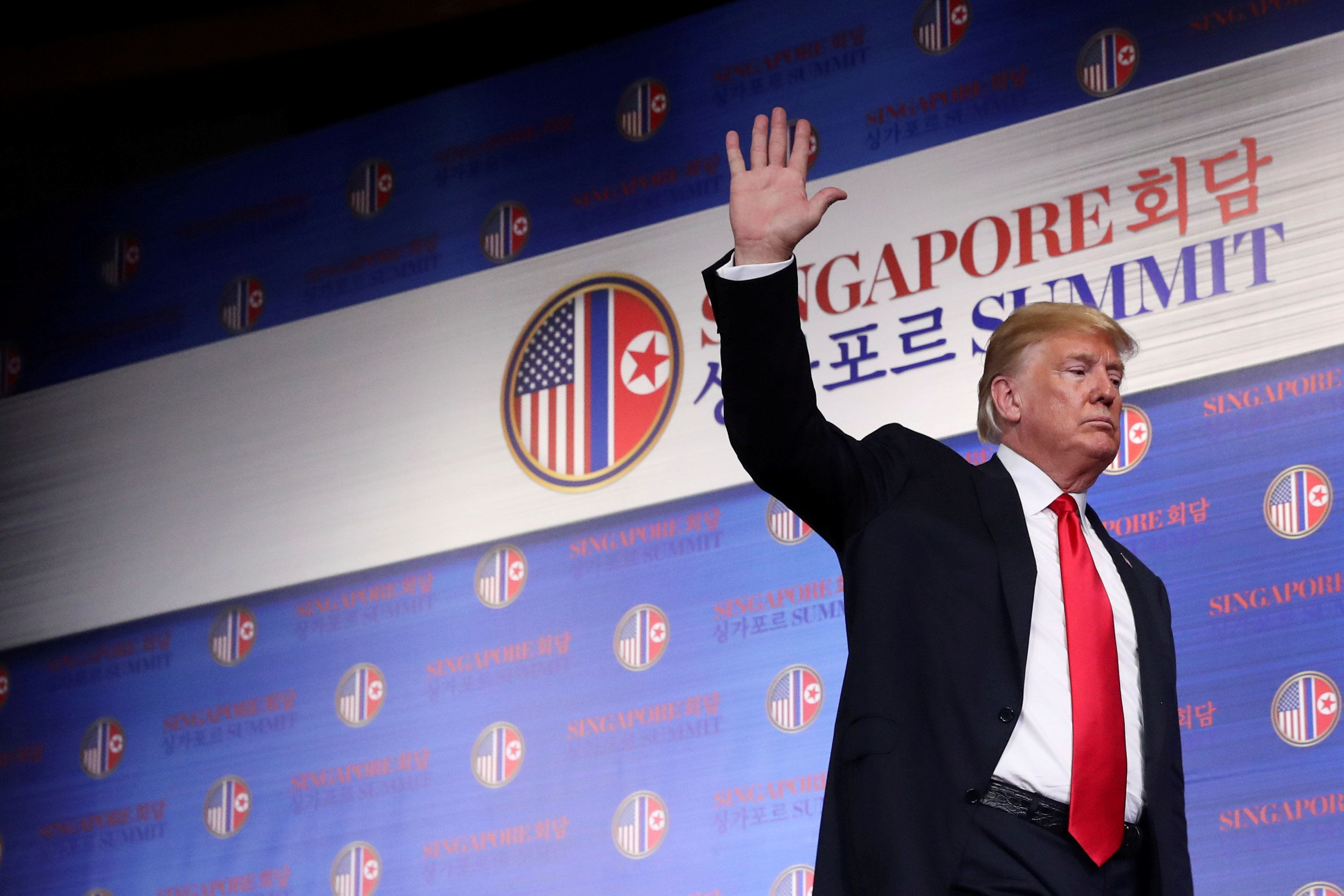 U.S. President Donald Trump waves after a news conference as a secret service agent walks at the Capella Hotel on Sentosa island in Singapore June 12, 2018. REUTERS/Jonathan Ernst     TPX IMAGES OF THE DAY
