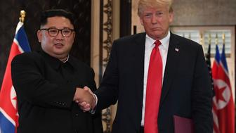 US President Donald Trump (R) and North Korea's leader Kim Jong Un shake hands following a signing ceremony during their historic US-North Korea summit, at the Capella Hotel on Sentosa island in Singapore on June 12, 2018. - Donald Trump and Kim Jong Un became on June 12 the first sitting US and North Korean leaders to meet, shake hands and negotiate to end a decades-old nuclear stand-off. (Photo by SAUL LOEB / AFP)        (Photo credit should read SAUL LOEB/AFP/Getty Images)