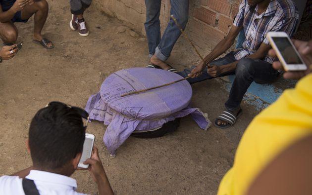 Des touristes et des consommateurs prennent des photos d'un fermier pendant l'extraction de la résine...