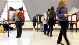 PORTLAND, ME - NOVEMBER 7: Sue Vittner, right, walks her completed ballot to the scanning booth at the Merrill Auditorium voting station Tuesday morning. Turnout at the station has been pretty good, according to Election Warden Carol . By 8:20 a.m., the site had processed ballots from 95 voters, which Morrissette estimated was already three times as many voters who cast ballots at the same station during the May election. (Staff photo by Ben McCanna/Portland Press Herald via Getty Images)