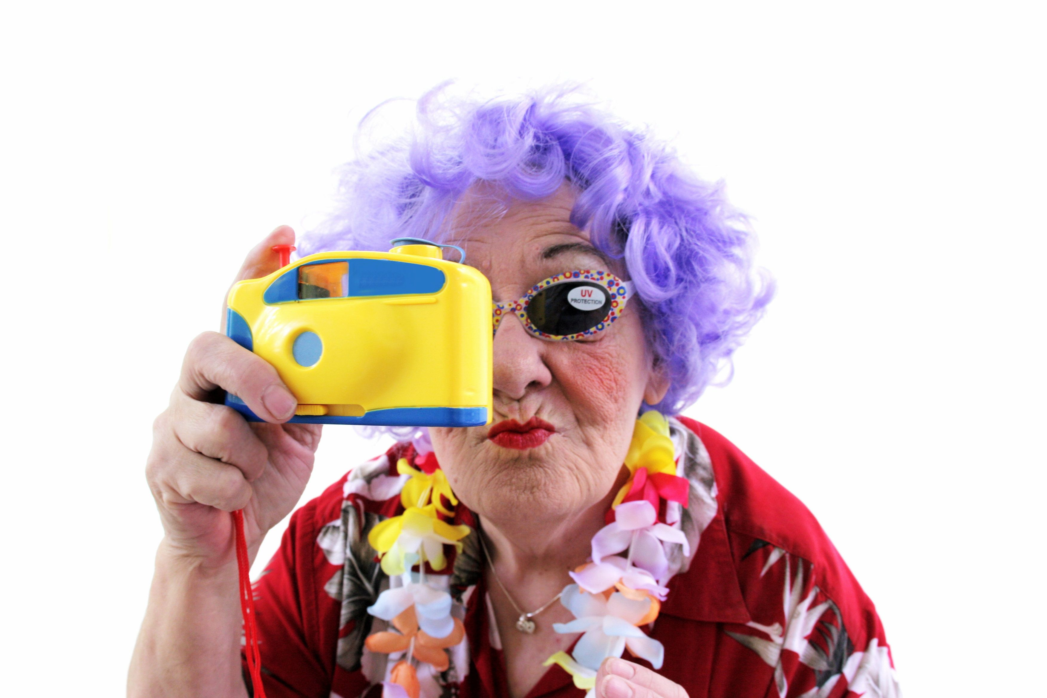 Purple haired crazy granny on white background. She's wearing a hawaiian shirt, lei, sunglasses with UV sticker and holding a toy camera. Part of a senior humor character series