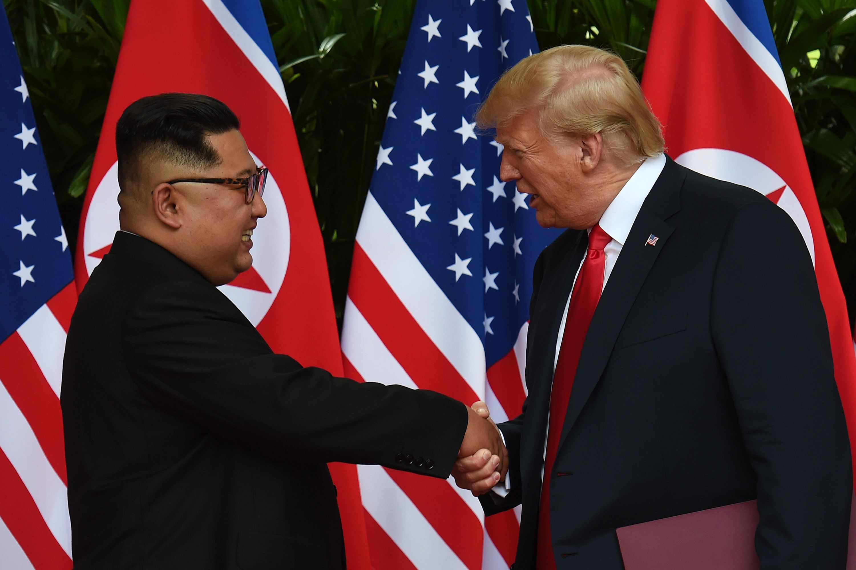 TOPSHOT - North Korea's leader Kim Jong Un (L) shakes hands with US President Donald Trump (R) after taking part in a signing ceremony at the end of their historic US-North Korea summit, at the Capella Hotel on Sentosa island in Singapore on June 12, 2018. - Donald Trump and Kim Jong Un became on June 12 the first sitting US and North Korean leaders to meet, shake hands and negotiate to end a decades-old nuclear stand-off. (Photo by Anthony WALLACE / POOL / AFP)        (Photo credit should read ANTHONY WALLACE/AFP/Getty Images)