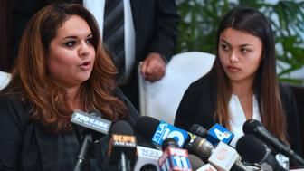Former USC student Angela Esquivel Hawkins (L) speaks as current University of Southern California (USC) student Daniella Mohazab (R) watches at a press conference with attorney Gloria Allred in Los Angeles, California on May 22, 2018. - A lawsuit has been filed against the University of Southern California (USC) on behalf of one of the students and calling on USC to conduct an independent investigation on allegations made by students alleging inappropriate conduct by Doctor George Tyndall, the gynecologist assigned to examine and treat USC students. (Photo by Frederic J. BROWN / AFP)        (Photo credit should read FREDERIC J. BROWN/AFP/Getty Images)