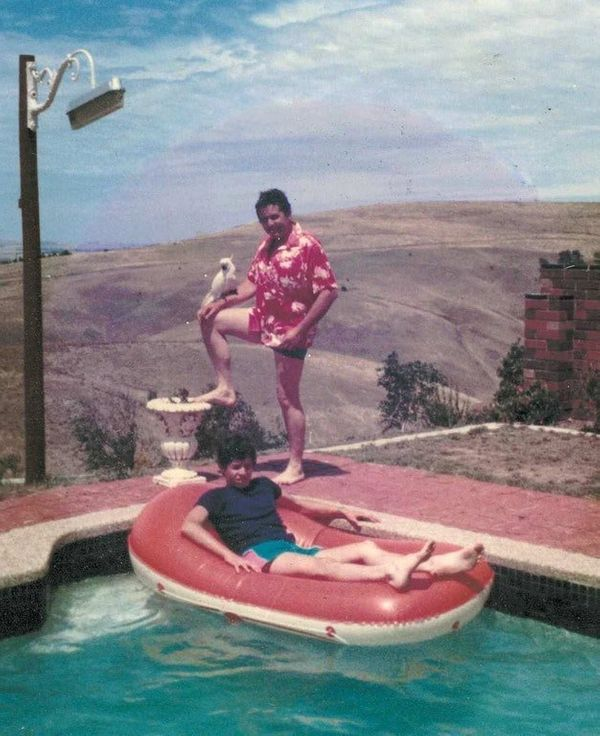 """My dad, Terry, with a Hawaiian shirt and cockatoo, with my brother on an upside-down inflatable boat in a swimming pool, wit"