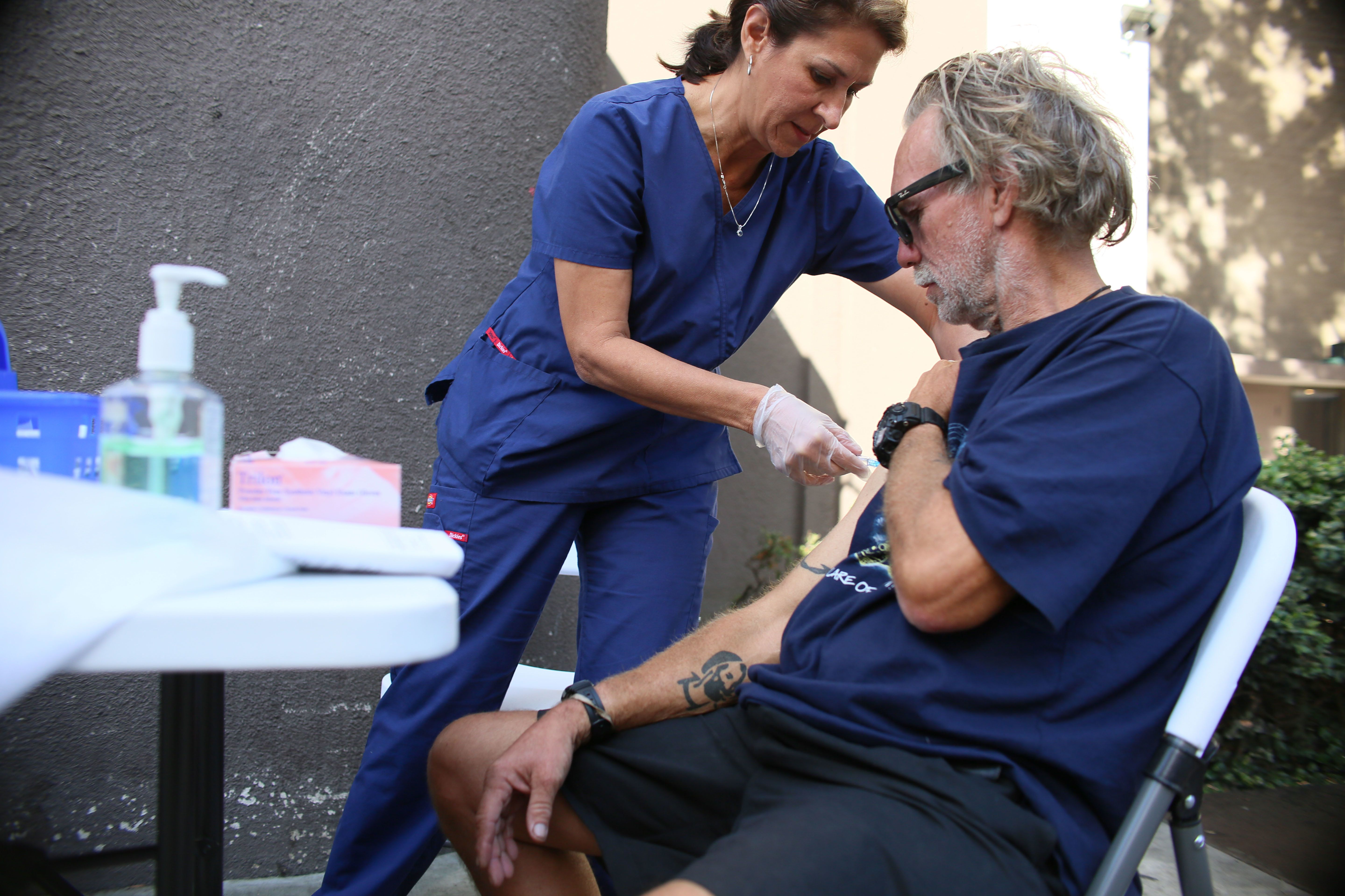 Paulina Bobenrieth a nurse with the HHSA Public Health dept. gives a Hepatitis A vaccine to a Homeless person in Downtown San Diego, CA on Wednesday, October 4, 2017.  A Hepatitis A outbreak has killed numerous homeless people and sent hundreds to the hospital.(Photo by Sandy Huffaker for The Washington Post via Getty Images)