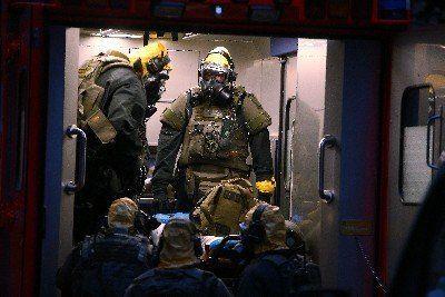 SEK Beamten mit Atemschutzmasken und Schutzanzügen steigen in einem Krankenwagen. Im Kölner Stadtteil Chorweiler stürmte die Polizei wegen des Verdachs auf Umgang mit giftigen Stoffen die Wohnung eines Mannes.