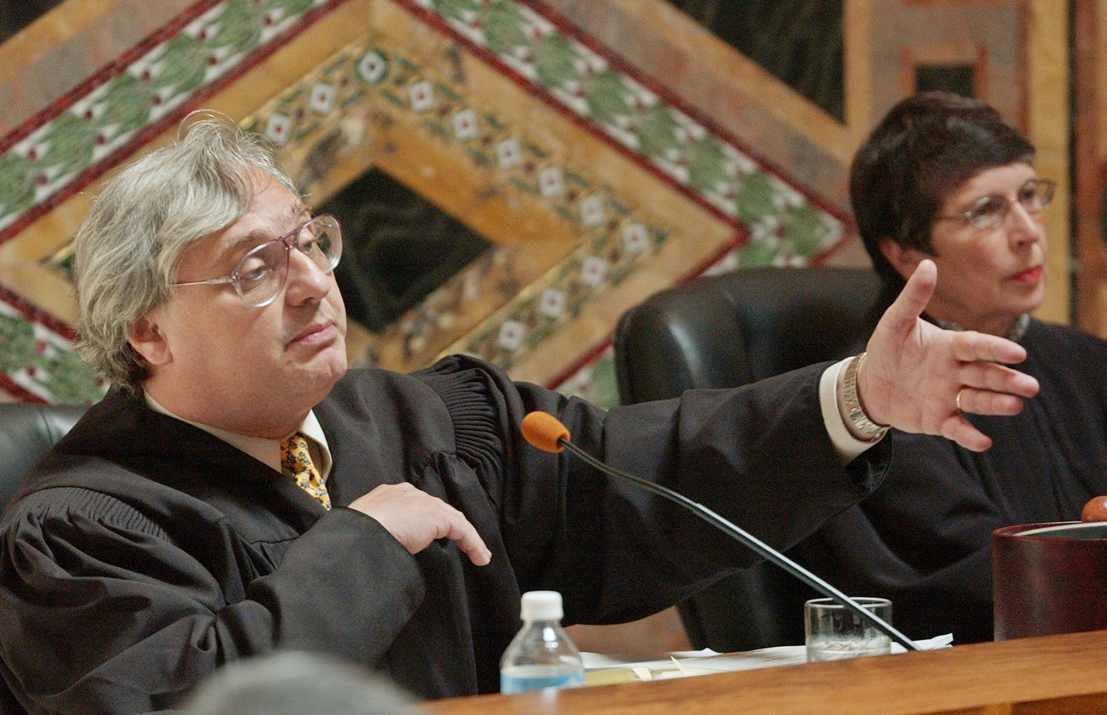 Judge Alex Kozinski, of the 9th U.S. Circuit Court of Appeals, gestures during oral arguments in San Francisco, September 22, 2003. Federal judges sharply and critically questioned lawyers defending a delay in California's October 7 gubernatorial recall election on Monday as an 11-member appeals court panel tried to decide whether to rescind an earlier ruling postponing the vote. The court's three Republican appointees, including Kozinski, led the questioning of American Civil Liberties Union attorneys Mark Rosenbaum and Lawrence Tribe in San Francisco. REUTERS/Paul Sakuma/POOL  PS/SV