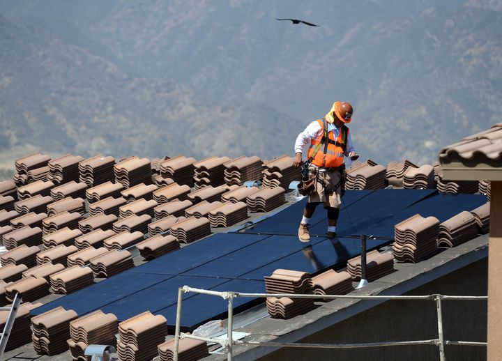 Workers install solar panels on the roofs of homes under construction south of Corona, California.