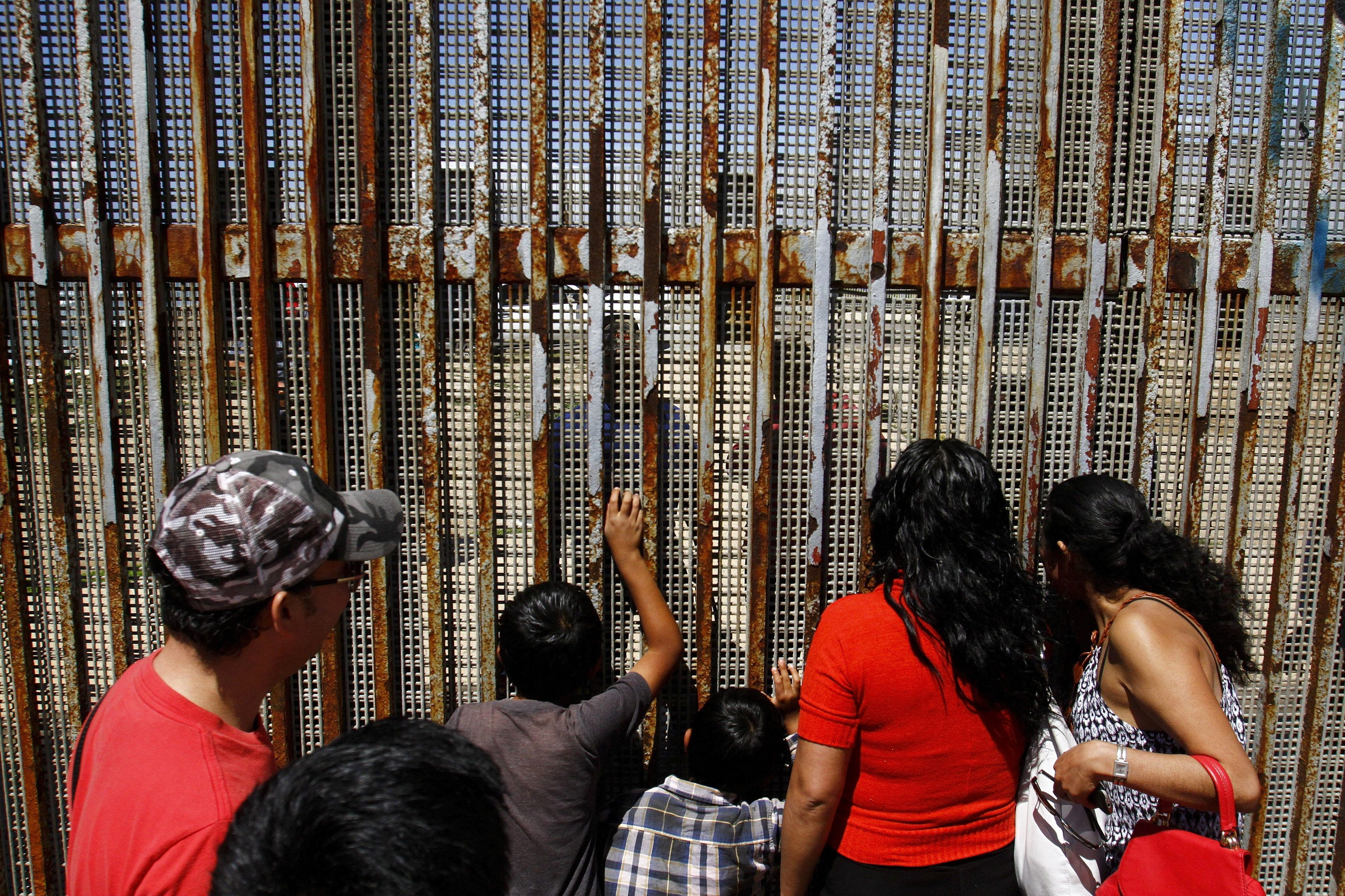 People talk to their relatives at a wall separating Mexico and the United States, as photographed from Playas Tijuana, in Tijuana, Mexico, April 10, 2016. Picture taken April 10, 2016. REUTERS/Jorge Duenes