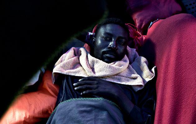Un inmigrante descansa sobre la cubierta del Aquarius cuando el barco se acerca a España. En la costa...