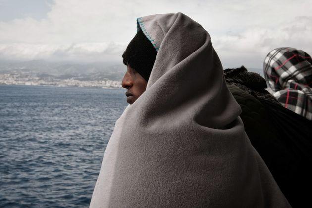 Ein Flüchtling blickt auf die Küstenlinie von