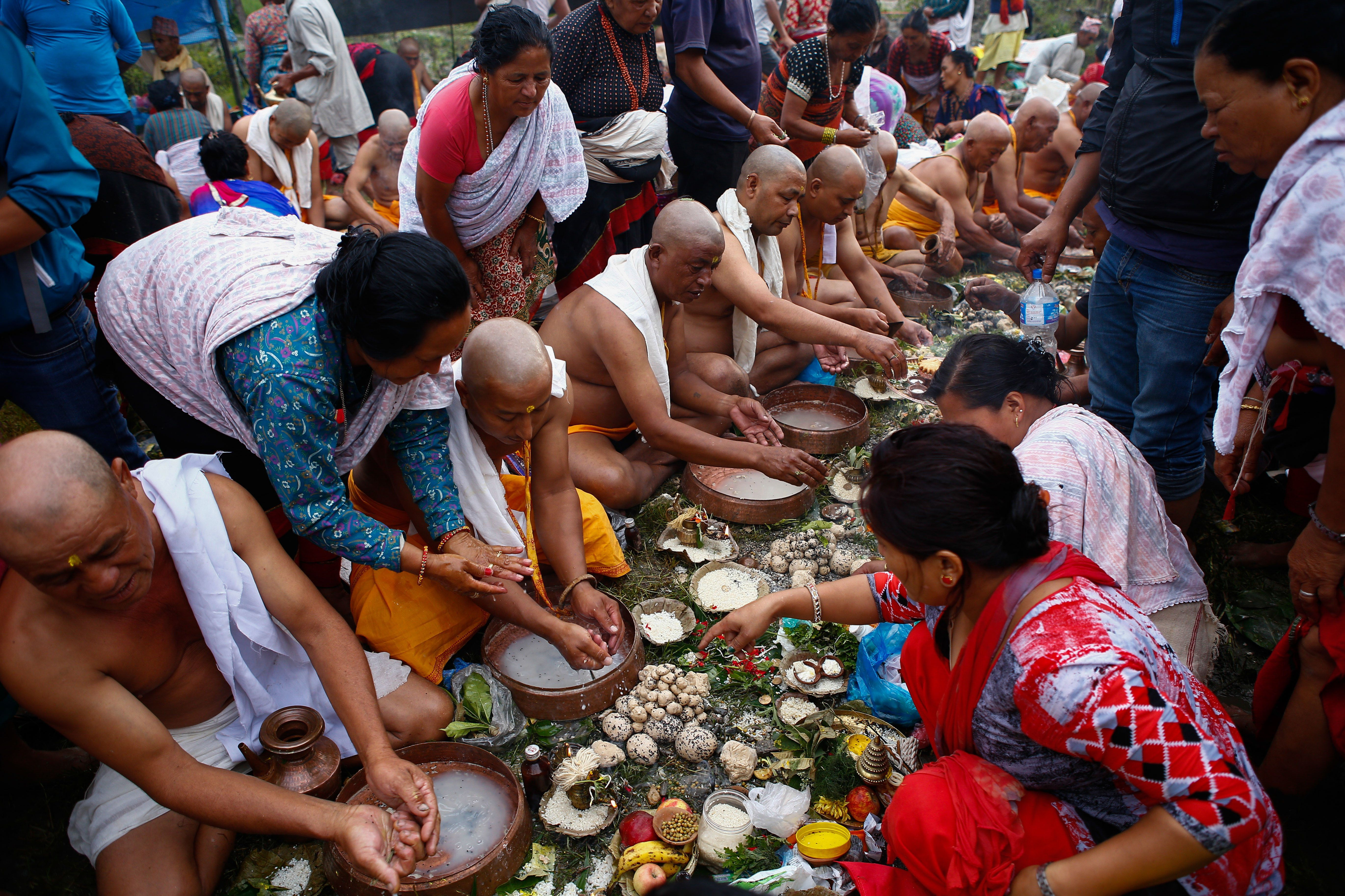 People perform rituals to honor their deceased fathers at a temple on the Bagmati River in Gokarna, Nepal.