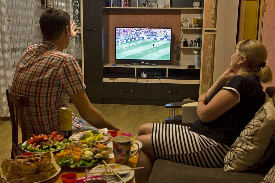 Anatolii and Julia in front of the TV watching the