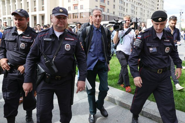 Gay rights campaigner Peter Tatchell (centre) is led away by Russian authorities in Moscow after staging...