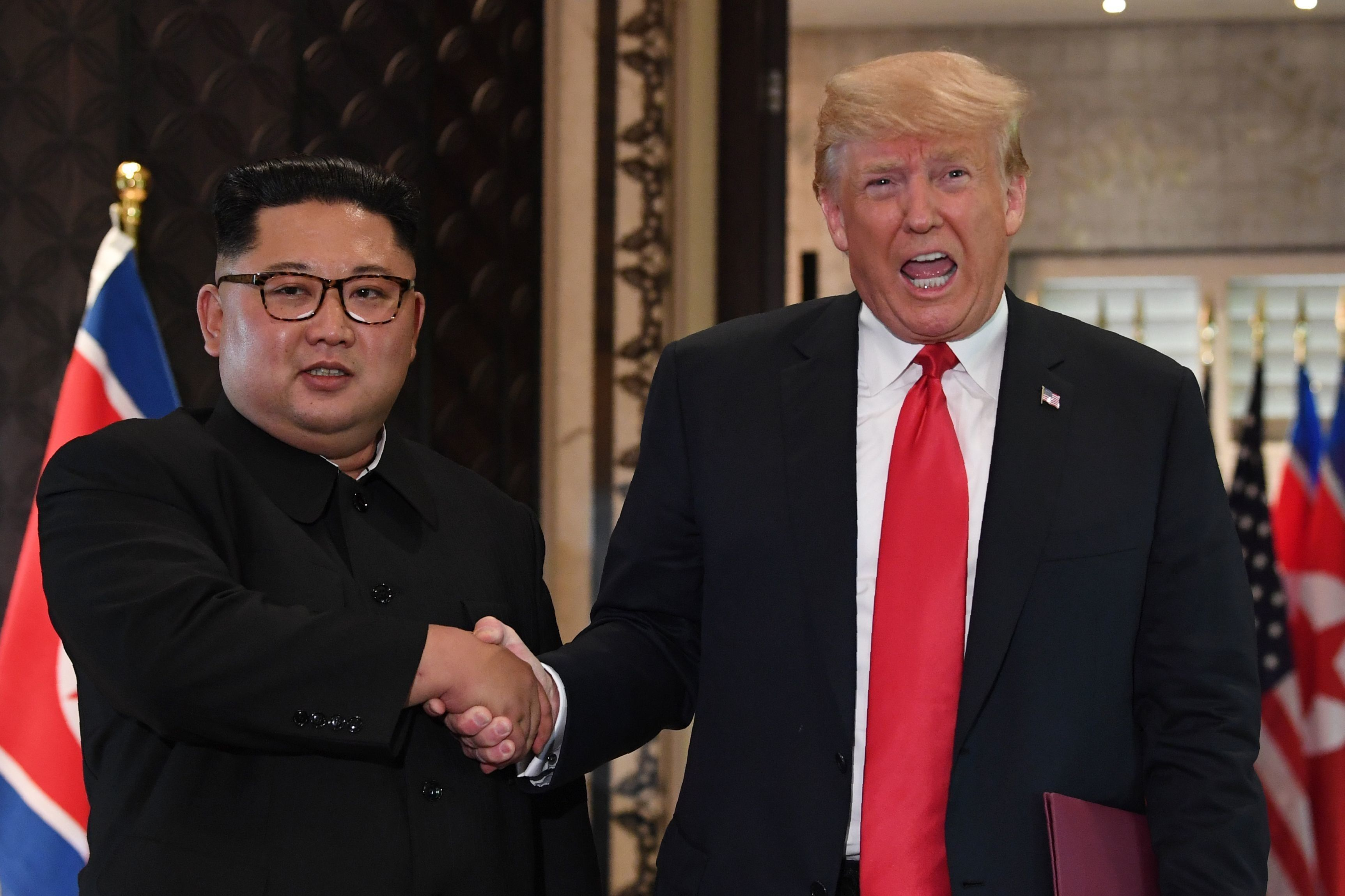 TOPSHOT - US President Donald Trump (R) and North Korea's leader Kim Jong Un shake hands following a signing ceremony during their historic US-North Korea summit, at the Capella Hotel on Sentosa island in Singapore on June 12, 2018. - Donald Trump and Kim Jong Un became on June 12 the first sitting US and North Korean leaders to meet, shake hands and negotiate to end a decades-old nuclear stand-off. (Photo by SAUL LOEB / AFP)        (Photo credit should read SAUL LOEB/AFP/Getty Images)