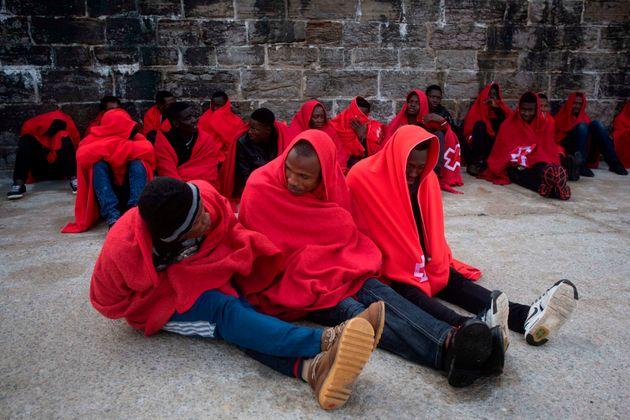 Des migrants se tiennent chaud sous les couvertures de la Croix Rouge, à leur arrivée au...