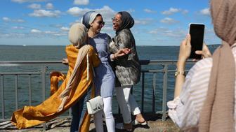 Maryam Said, 19, Eman Gad, 20, and Hallah Towfiek, 20, get their photos taken after morning prayers to mark Eid Al-Fitr at Bensonhurt Park in Brooklyn, New York, U.S., June 15, 2018. REUTERS/Gabriela Bhaskar
