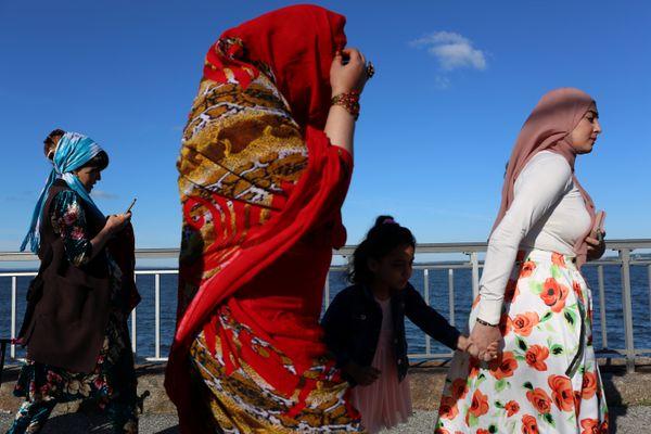 Muslim women walk along the boardwalk at Bensonhurst Park on June 15.
