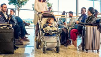 Woman with toddler in stroller and a group of other people sitting in a an airport waiting room.